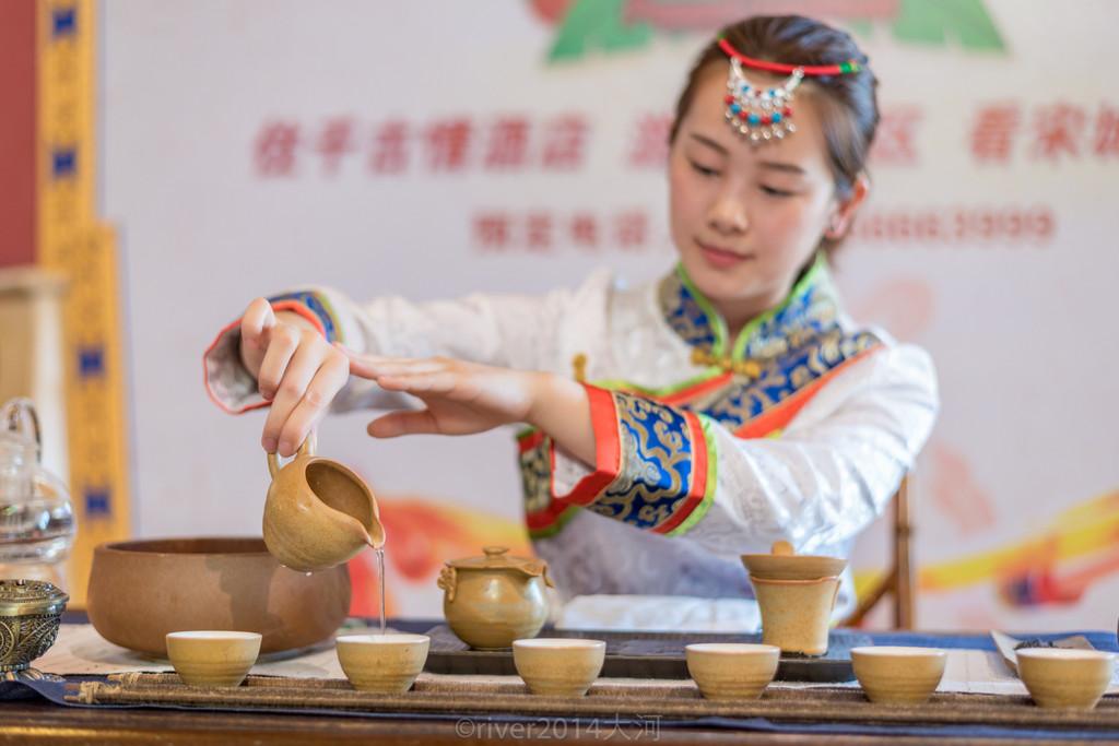 大堂,身着藏式服装的姑娘正在表演茶艺迎宾.图片