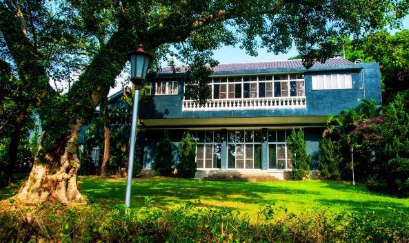 "<p class=""inset-p"">士林官邸是蒋介石在台湾住的时间最长的行馆,背有福山倚靠,又紧邻中山北路,可快速抵达总统府,现在士林官邸已改为台北市的生态公园,是市民亲近绿地和休闲的好去处。</p><p class=""inset-p"">士林官邸是一座两层楼的西式小洋房,进门迎面是一尊大型龙凤根雕玄关,穿堂墙上挂4幅宋美龄亲笔国画复制品,桌椅家具中西合璧,地铺暗红地毯。洋房内陈设典雅简朴,一楼是会客厅,二楼是蒋公夫妇卧室。</p><p class=""inset-p"">穿堂之后是小客厅,壁炉上方悬挂着蒋介石母亲王采玉的油画遗像,蒋介石常在这里与儿孙下跳棋、围棋,享受天伦之乐。小客厅也兼做电影室,蒋介石夫妇常坐前排,亲友宾客陪坐后座,一同观看香港、欧美进来的新影片。餐厅有西式长桌和中式圆桌各一张,人少时就在圆桌用餐。1952年扩建的大客厅地方宽广,布置了4个中西式会客区。墙上有西式壁炉,还有4个苏州园林风格的大圆窗,其中3个可以饱览内花园秀色,1个则嵌贴宋美龄手绘的画作。</p><p class=""inset-p"">紧邻洋房的士林园艺致力于兰花培植,中式庭园位于蒋公公馆对面,里面的拱桥、曲池、流水等东方庭园造景,令人彷佛置身古代中国。欧式花园中有温室盆栽区及玫瑰园,据说是蒋夫人最喜爱的花园,院里的苗圃、花艺、雕塑、水池都洋溢这浓浓的西方风情。中西两种风格同时聚合在一个地方,并没有显得突兀和怪异,却有种别样的美。</p><p class=""inset-p"">官邸出口处有一座咖啡馆,很多人都坐在咖啡馆门口的露天吧区内休憩闲谈,咖啡馆的招牌是一张很大的黑白照片,照片上身穿婚纱的宋美龄和西装革履的蒋介石含笑相依,这是1927年12月1日蒋介石与宋美龄在上海大华饭店举行的世纪婚礼上的照片。参观完官邸后,不妨来此小坐一下。</p>"